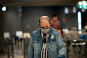 A man wears a protective mask upon his arrival from Dubai after a 14-hour flight on Emirates flight 231, at the international terminal at Dulles International Airport in Dulles, Va., Monday, March16, 2020. Some people are taking the precaution of wearing face masks as they arrive to be greeted by family and or friends. Credit: Rod Lamkey / CNP