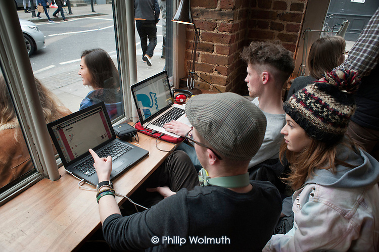 Customers work on laptops in the Fix186 cafe in Shoreditch, London, a run-down commercial district  also known as Silicon Roundabout, which is undergoing gentrification as it becomes a centre for web-based companies and IT start-ups.
