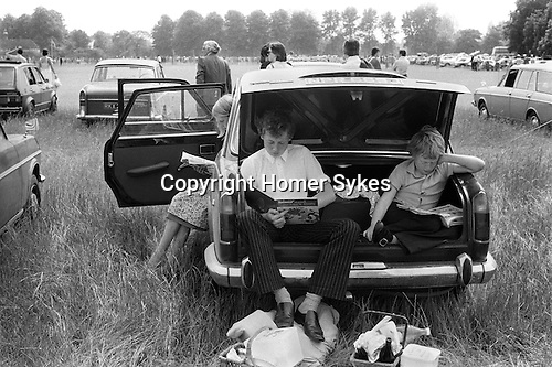 Eton, Berkshire. 1978<br /> The remains from a family picnic lie scattered on the ground, the inter-house cricket match on Agar's Plough has resumed. A young Etonian could not care less, he's engrossed in a copy of Asterix and Caesar's Gift the twenty first volume in the series.