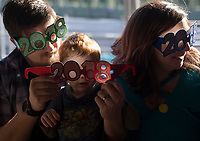 NWA Democrat-Gazette/CHARLIE KAIJO Michael Prestien, Lucas Prestien 2 and Sara Prestien of Bentonville (from left) try on New Year's glasses during the Noon Year's Eve event on Sunday, December 31, 2017 at Crystal Bridges in Bentonville. Visitors rang in the New Year (without staying up past bedtime) at the third annual family celebration including arts projects, performances and a family dance party.