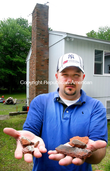 MIDDLEBURY, CT. 06 June 2006-060606SV01--Rob Bona of Middlebury holds some of the bricks that fell off his mothers chimney due to blasting from a near by development.<br /> Steven Valenti Republican-American