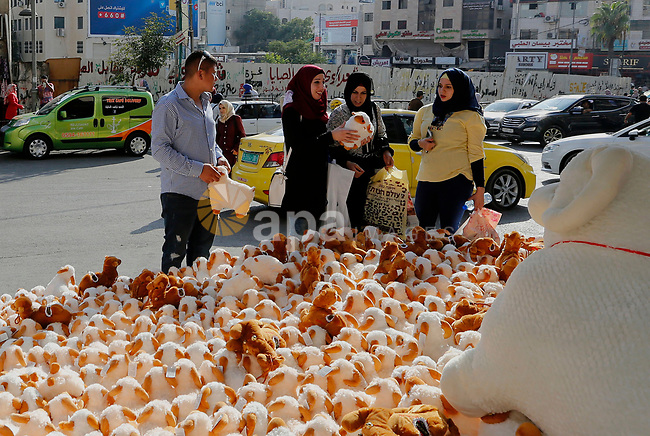 Palestinians buy toys of sheep at a market ahead of the Eid al-Adha festival in the West Bank city of Hebron, on August 21, 2017. Photo by Wisam Hashlamoun