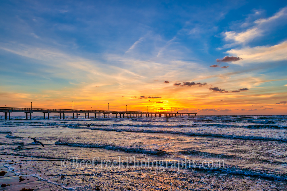 Another gorgeous capture of the Texas coast at sunrise with the sand and waves creating ripples in the sand and the beautiful waters with their gentle waves and wonderful surf to entice us in as the sun gently rises over the Caldwell fishing pier with these wonderful colors of red, pink, orange and blues make for a beautiful.