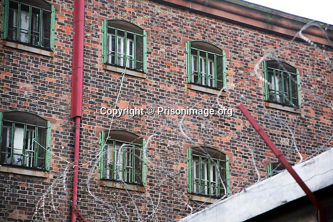The cell windows of one of the wings at Liverpool prison, watched over by a camera in the courtyard. HMP Liverpool in Merseyside, United Kingdom was built in 1855 and is one of the largest prisons in Western Europe. It has a capacity of 1393 prisoners, who are spread over eight wings.