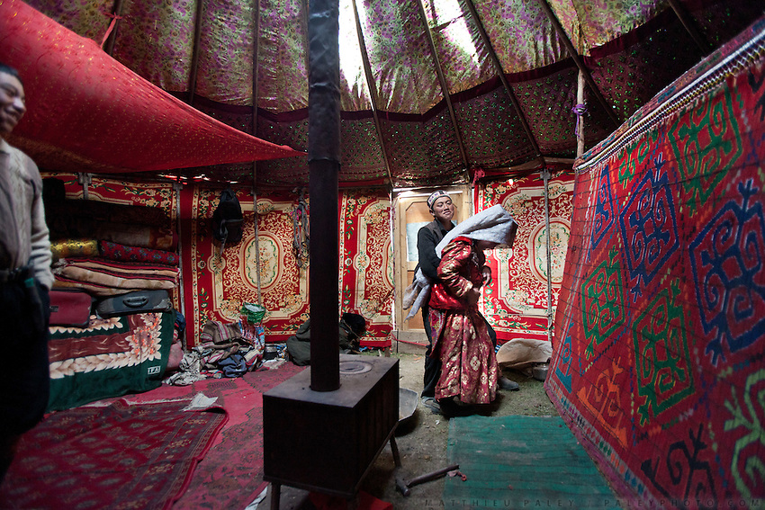 Inside the young married couple of Nemat Ullah and Woolook Bu's yurt. They are playing around in front of Nemat's brother (left)...Daily life at the Khan (chief) summer camp of Kara Jylga...Trekking through the high altitude plateau of the Little Pamir mountains (average 4200 meters) , where the Afghan Kyrgyz community live all year, on the borders of China, Tajikistan and Pakistan.