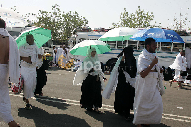 Muslim pilgrims stand at Mount Arafat, southeast of the Saudi holy city of Mecca, on November 15, 2010. Pilgrims flooded into the Arafat plain from Mecca and Mina before dawn for a key ritual around the site where prophet Mohammed gave his farewell sermon on this day in the Islamic calendar 1,378 years ago. Pilgrims spend the day at Arafat in reflection and reading the Koran or Mulsim holy book. Photo by Mahfouz Abu Turk