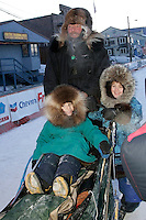 Thursday  March 15, 2007   ---- Nome, Alaska.   Sonny Linder's son Sam (3) and daughter Sarah (6) get a ride on their dad's sled to the dog yard after Sonny arrived in 25th place.