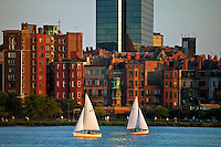 Brownstones around the base of the Hancock Tower with two ailboats on the Charles River at sunset Boston M