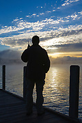 Wellington State Park - The silhouette of a man on dock watching sunrise over Newfound Lake in Bristol, New Hampshire USA talking on cell phone.