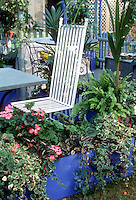 Raised bed container garden with annuals, flowers and foliage, patio with chair, houseplants, small patio with table, blue color theme, geraniums, ivy, swedish ivy, white chair furniture