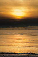 The sun sets over Cook Inlet and Alaska's Kenai Beach as an ice fog rolls in on a cold winter's day.