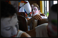 Luisito Ortiz (left) and Carlos Malgarejo (far right)  are seen in the bus as Contrafarsa makes it's way to the inaugural parade of the Uruguayan Carnival. For more than a month, every night after the parade, the Contrafarsa members travel in the same bus from neighbourhood to neighbourhood,  to perform in the tablados ( a neighbourhood theatre built specially for the Carnival) in Montevideo, the capital city of Uruguay