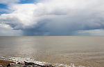 Heavy rain falling from dark clouds over the North Sea coast, Suffolk, England