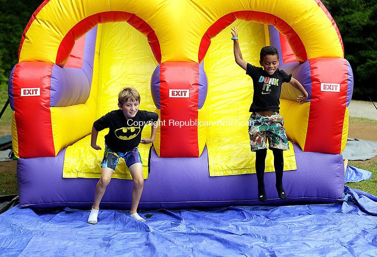 "Torrington, CT- 27 July 2017-072717CM02-  Hayden Barnett 9, left, and Joey Collins, 7, both of Torrington slide off a giant bounce house obstacle course during the  annual Camp Moe Carnival in Torrington on Thursday.  The annual carnival honors Emil ""Moe"" Renzullo, a camper, who passed away in 2010 after a long battle with Leukemia.       Christopher Massa Republican-American"