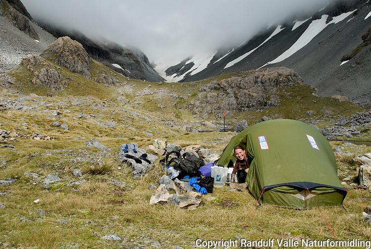 Jente i åpningen av telt. ---- Girl in tent opening.