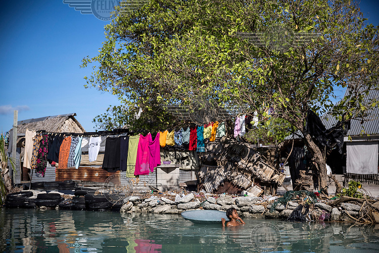 A girl bathes near her family's house during a high tide. The village is regularly flooded during high tides despite residents attempts to build sea walls or take care of those that were built by the local government, but frequent big waves continue to damage them, putting resident's houses, and gardens under the constant threat.