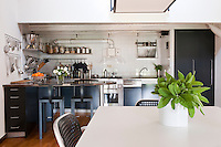 A contemporary kitchen produced by Driade makes full use of the limited space by using clever storage and a slim breakfast bar