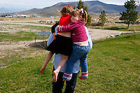 Two girls get a piggy-back ride from their father. Salt Lake County - Suburban polygamist family, one man, three wives, and twenty-one children living in the Salt Lake Valley; 4.01.2007