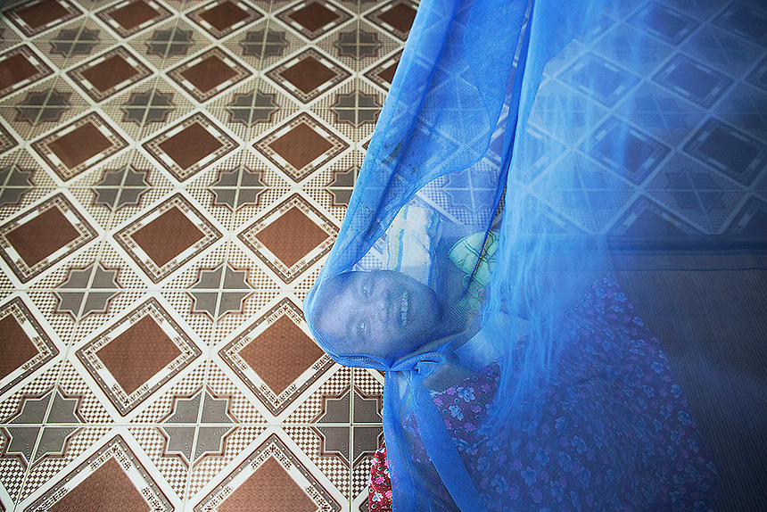 Lai Van Manh, a second generation Agent Orange victim, smiles under the mosquito net in the family house in Tuong An village, in Thai Binh province in northern Vietnam April 9, 2015. Lai Van Manh's father, a former intelligence officer in the North Vietnamese army said that he served during the Vietnam War in the area heavily contaminated by use of the Agent Orange. Him and his wife now take care of their two physically and mentally handicapped sons whose health condition family and officials link to the effects of the Agent Orange.  REUTERS/Damir Sagolj