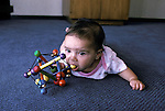 San Diego CA Latina baby sucking on rattle toy, five-months-old