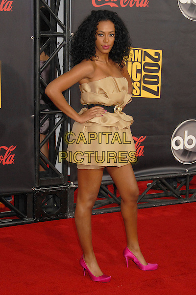 SOLANGE KNOWLES.2007 American Music Awards at the Nokia Theatre LA Live, Los Angeles, California, USA..November 18th, 2007.full length black belt pink shoes beige gold dress layers layered strapless hand on hip.CAP/ADM/BP.©Byron Purvis/AdMedia/Capital Pictures.