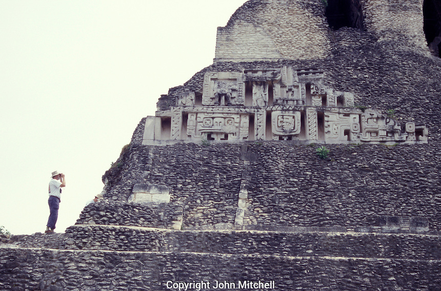 Tourist photographing the west frieze of El Castillo, the main structure at the Mayan ruins of Xunantunich near the town of San Ignacio, Cayo District, Belize