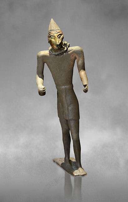 Hittite bronze figure with a mask, Hittite Period. Adana Archaeology Museum, Turkey. Against a grey art background
