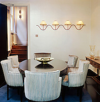 A contemporary dining room with an oval ebony table with dining chairs designed by David Collins upholstered in blue and silver silk by Missoni. The 1950s lights are by Jean Royere.