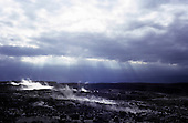 Big Island, Hawaii. Steam venting from barren volcanic landscape of Kilauea Caldera strewn with black lava rocks.