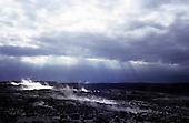 Big Island, Hawaii. Steam venting from barren volcanic landscape of Kilauea Caldera strewn with black lava rocks.