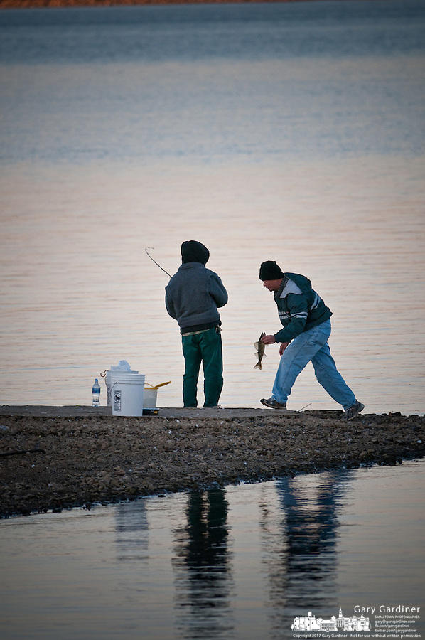 Fishermen a stand on a narrow slit of land where they fish a as the sun sets in the fall. One carries a saugeye he caught