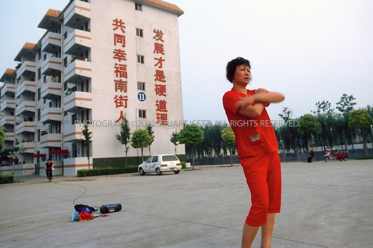 """7/15/2005--Nanjie Village, Henan Province, China..A villager does her morning excercises in front of a sign that reads: """"The people of Nanjie Village are happy together and only through development can we reach the truth"""" in Nanjie village, a model communist village in the central province of Henan. It collectivised its agricultural production and industry in the mid 1980s - when the rest of the country was doing the opposite, introducing market reforms put forward by former leader Deng Xiaoping. ..It continues to be run on Maoist egalitarian lines and has become something of a tourist attraction because of its staunch adherence to the values of the past. .Photograph By Stuart Isett.All photographs ©2005 Stuart Isett.All rights reserved."""