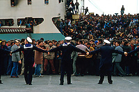 Brindisi, 8 Marzo, 1991. Militari della Marina tentano di contenere la spinta degli immigrati Albanesi ammassati all'interno del porto di Brindisi. Migliaia di Albanesi arrivarono al porto di Brindisi utilizzando ogni tipo di imbarcazione, dopo la caduta del regime comunista in Albania. Italian Navy members try to close one of the gate of Brindisi harbor after thousands of albanian refugees reached Italy. It was March 8, 1991 when thousands of albanian refugees reached Italy after the fall of the comunist regime. The city of Brindisi, south Italy was invaded by a mass of desperate and poor people.