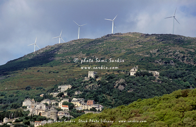Wind turbines on a mountain top above Rogliano Village, Corsica Island, France.