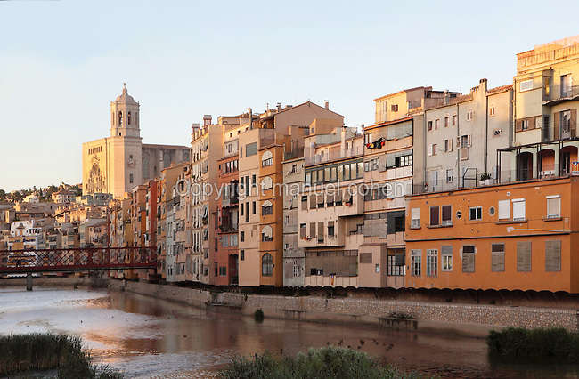 Santa Maria Cathedral or Cathedral of St Mary of Girona, Eiffel bridge and houses overlooking the river Onyar in the town of Girona, at the confluence of the rivers Ter, Onyar, Galligants and Guell, Catalonia, Spain. The cathedral was begun in the 11th century in Romanesque style, and later continued in the 14th century in Catalan Gothic style, redesigned by Pere Sacoma in 1312 and built by the school of Mallorcan architect Jaume Fabre. Of the original Romanesque building only the 12th century cloister and a bell tower remain. The cathedral was completed in the 18th century. Here we see the Baroque facade and new octagonal bell tower, begun in 1590 and completed in the 18th century, which houses 6 bells. Picture by Manuel Cohen