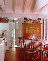 This red and white country-style kitchen has a cupboard against one wall decorated with fishing scenes