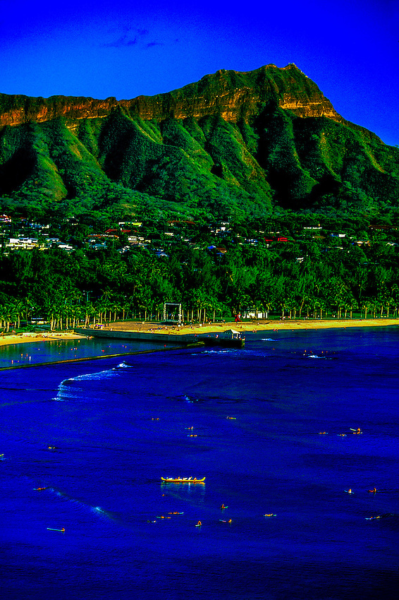 Surfers wait in water along Waikiki Beach with Diamond Head Crater in background, Honolulu, Hawaii USA