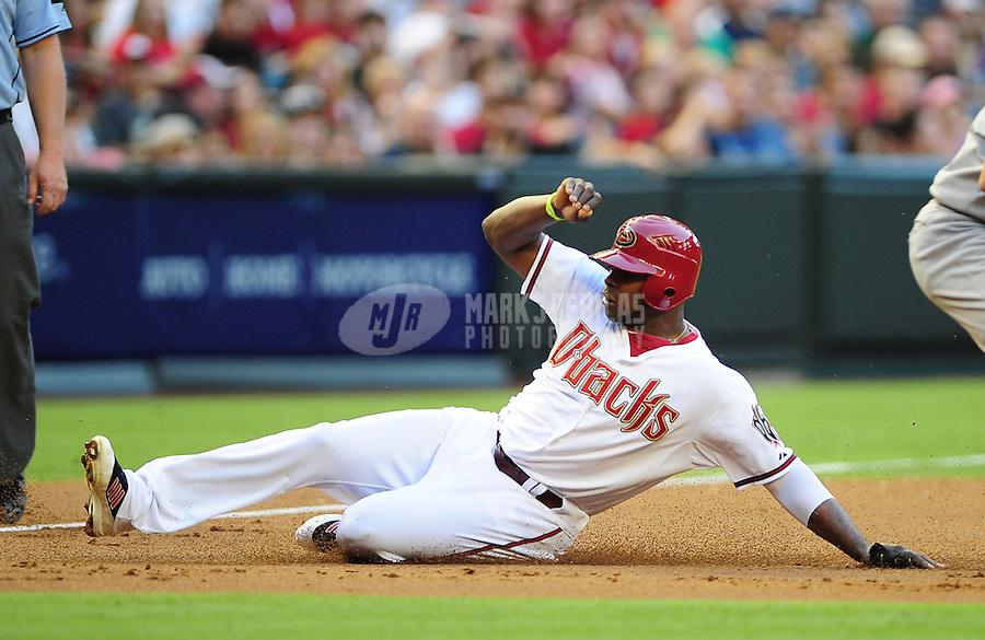 Jun. 8, 2012; Phoenix, AZ, USA; Arizona Diamondbacks outfielder Justin Upton slides safely into third base in the first inning against the Oakland Athletics at Chase Field.  Mandatory Credit: Mark J. Rebilas-