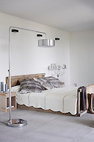 The master bedroom is an airy, white space with simple wooden bedroom furniture. Overhead lighting is provided by a stainless steel floor lamp.