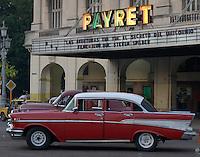 red Bel Air Chevrolet oldtimer american car, in front of Payret Cinema lights ,  Havana, Cuba