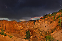 730750180 lightning from a summer monsoon thunderstorm flashes over natural bridge in bryce canyon national park utah united states