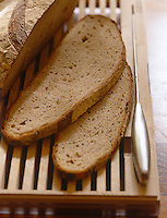 Detail of fresh brown bread cut into slices on a wooden breadboard.