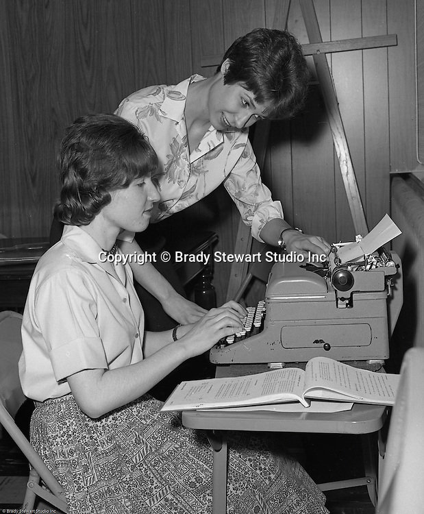 Pittsburgh PA:  Instructor helping a young woman with office typing skills at Goodwill Industries - 1966.  <br />