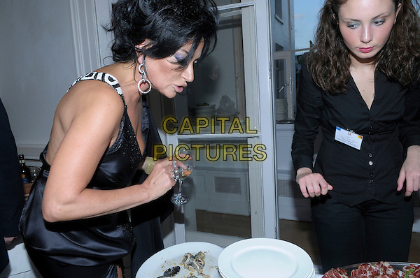 Nancy Dell'Olio  .The catwalk show of Nico Didonna at The Italian Culture Institute in Belgravia, London, England..20th July 2012.half length black dress side profile food beverage.CAP/IA.©Ian Allis/Capital Pictures.
