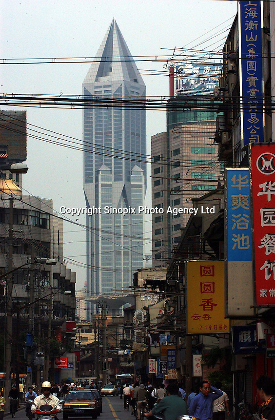 An old district in Shanghai in dwarfed by a Marriot Hotel, China. .
