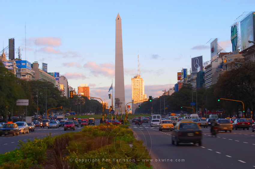 The obelisk, obelisco, on the Plaza de la Republica Square on the Avenida 9 Julio Avenue of ninth of July, taxis and cars in the foreground. Traffic. Modern office buildings. at sunset. Buenos Aires Argentina, South America