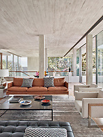 The contemporary home has a relaxed, peaceful quality with a seamless connection between indoor and outdoor living. The main floor is a large open-plan space that connects the dining room and the living room. Concrete is used in the ceilings and walnut wood floors add warmth.