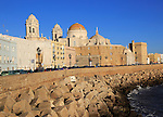 Coastal view east of rock armour coastal defences and cathedral, Cadiz, Spain