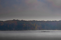 A rowing team practices on fog shrouded Hoover Reservoir as the sun begins to rise on a Saturday morning.