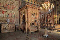 Bedroom of Anne of Austria, 1601-66, wife of King Louis XIII, Chateau de Fontainebleau, France. The room is decorated by Charles Errard and Gilbert de Seve c. 1660. The Renaissance style sculpted walnut furniture, (four-poster bed, 2 bedside tables, 2 commodes, a console sofa, 6 armchairs, 6 chairs and 2 footstools) was delivered in 1860 by the house of Fourdinois. The 2 tapestries depict the Triumph of Mars and the Triumph of Religion, from cartoons by Noel Coypel, 1628-1707. The Palace of Fontainebleau is one of the largest French royal palaces and was begun in the early 16th century for Francois I. It was listed as a UNESCO World Heritage Site in 1981. Picture by Manuel Cohen